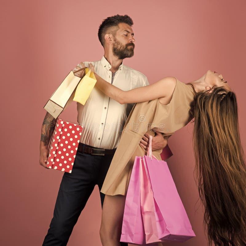在爱的夫妇在桃红色墙壁附近拿着购物袋 免版税库存照片