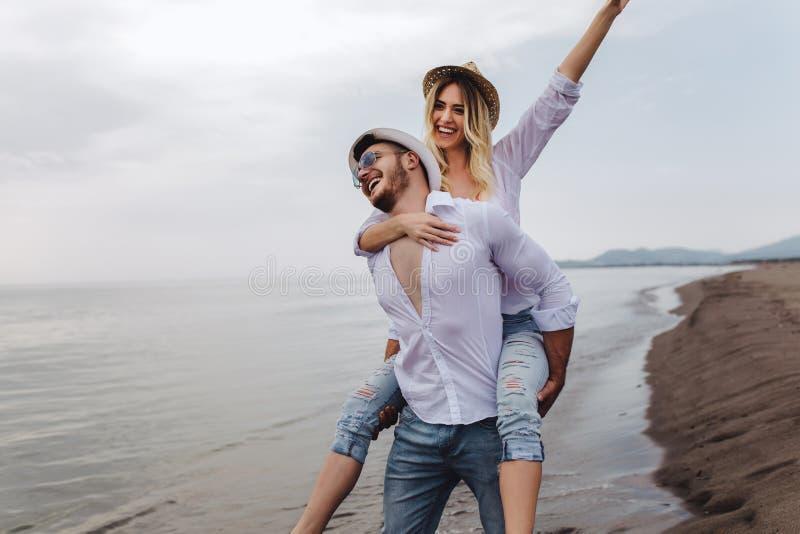 在爱的夫妇在海滩暑假 扛在肩上在年轻男朋友的快乐的女孩获得乐趣 库存照片