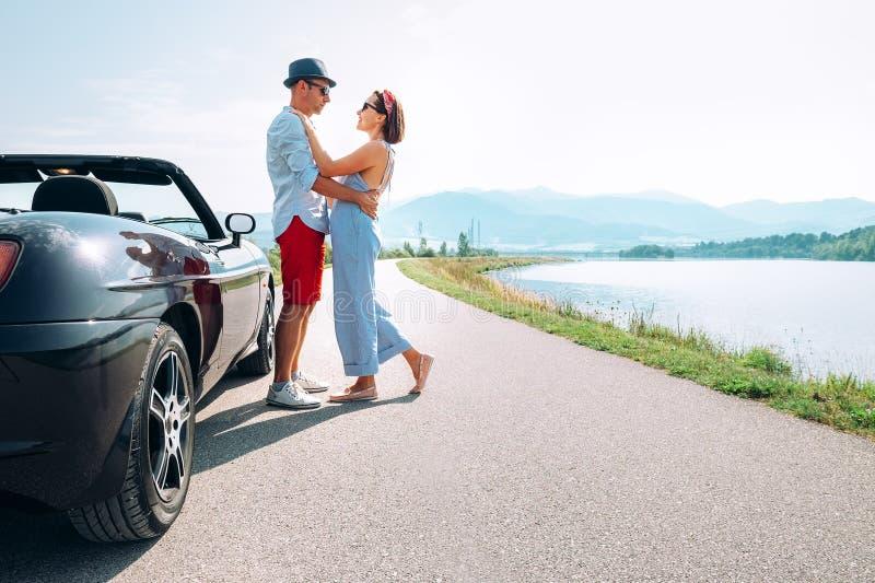 在爱的夫妇在美丽如画的敞蓬车汽车附近站立 免版税图库摄影