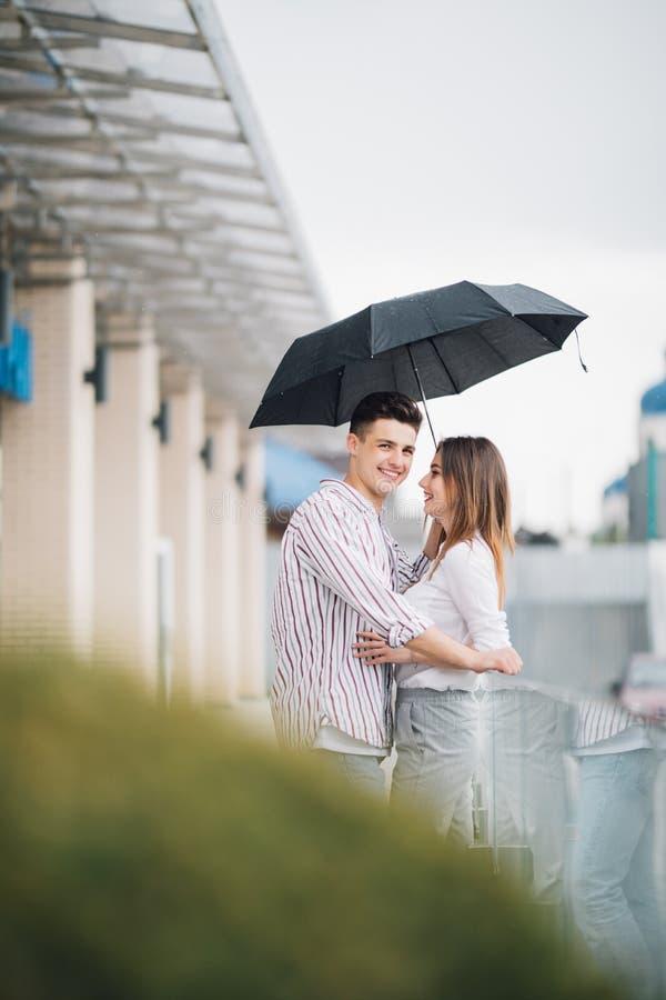 在爱的夫妇在街道上在一下雨天 步行沿着向下街道阳台的朋友 免版税库存照片