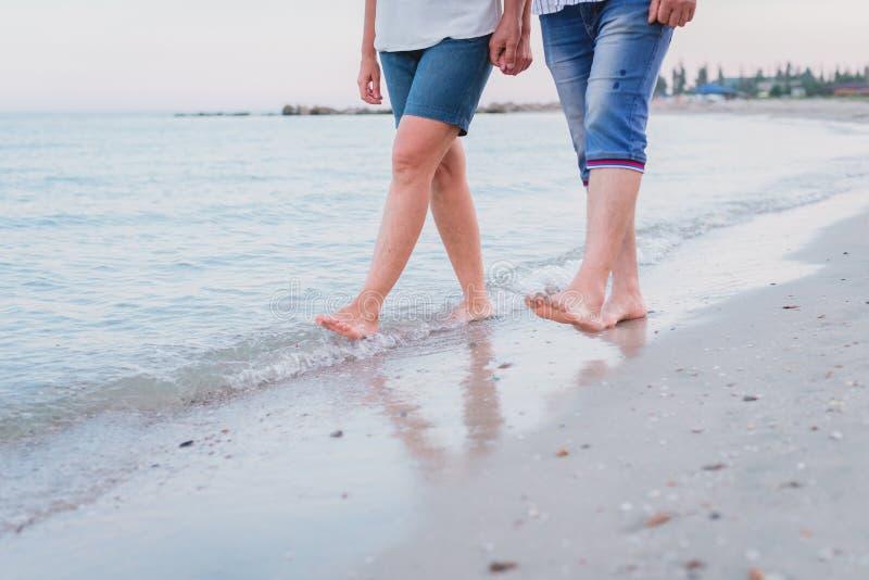 在爱的夫妇握他们的手并且沿海海滩赤足走 免版税库存图片