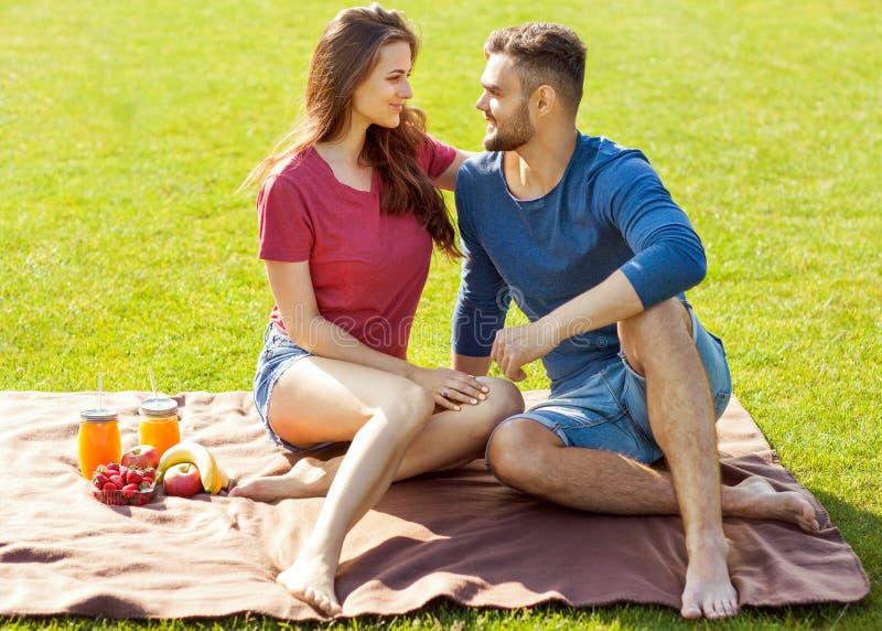 在爱的夫妇获得乐趣在公园并且喝圆滑的人和eati 免版税库存图片