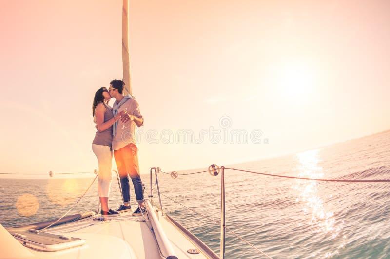 在爱的富有的年轻夫妇在欢呼在日落的风船 免版税库存照片