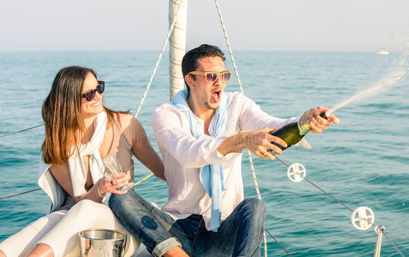 在爱的年轻夫妇在欢呼与香槟酒瓶的帆船-愉快的女朋友生日宴会巡航旅行 免版税库存图片