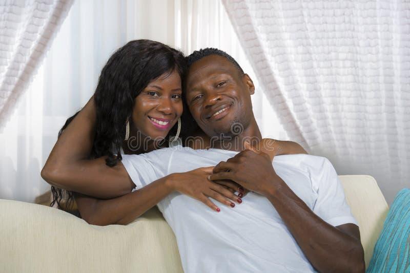 在爱的年轻美好和愉快的黑美国黑人的夫妇放松在现代家庭在沙发长沙发的客厅拥抱的甜点 库存图片