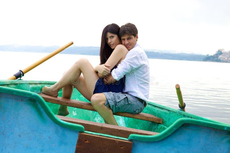在爱的愉快的夫妇在一点小船的假期 库存图片