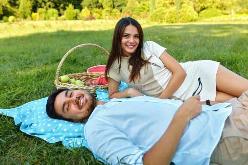 在爱的愉快的夫妇在浪漫野餐在公园 关系 免版税库存照片