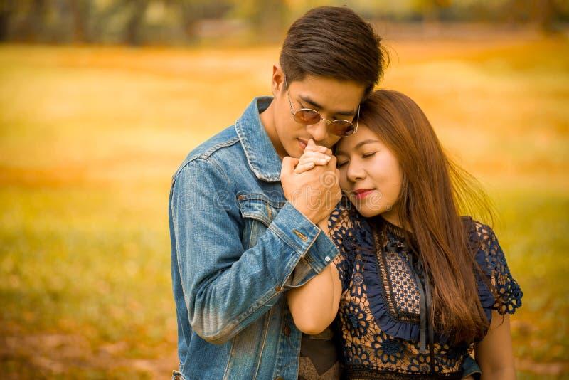 在爱的愉快的年轻亚洲夫妇拥抱的男朋友亲吻和拿着手女朋友在秋天公园 免版税库存照片