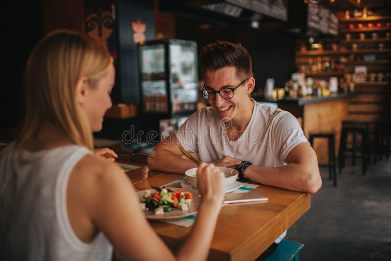 在爱的愉快的年轻夫妇有一个好日期在酒吧或餐馆 他们讲关于他们自己的有些故事 免版税库存图片