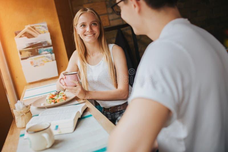 在爱的愉快的年轻夫妇有一个好日期在酒吧或餐馆 他们讲关于他们自己的有些故事 库存照片