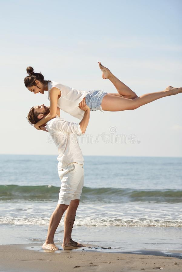 在爱的愉快的年轻浪漫夫妇获得在美丽的海滩的乐趣美好的夏日 免版税库存图片