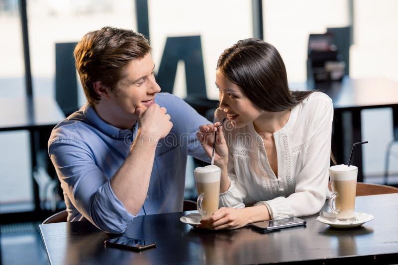 在爱的愉快的年轻夫妇在浪漫日期在餐馆 库存照片