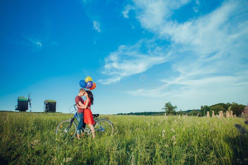 在爱的愉快的年轻成人夫妇在领域 微笑和休息在自行车骑马以后的两,男人和妇女 免版税库存照片