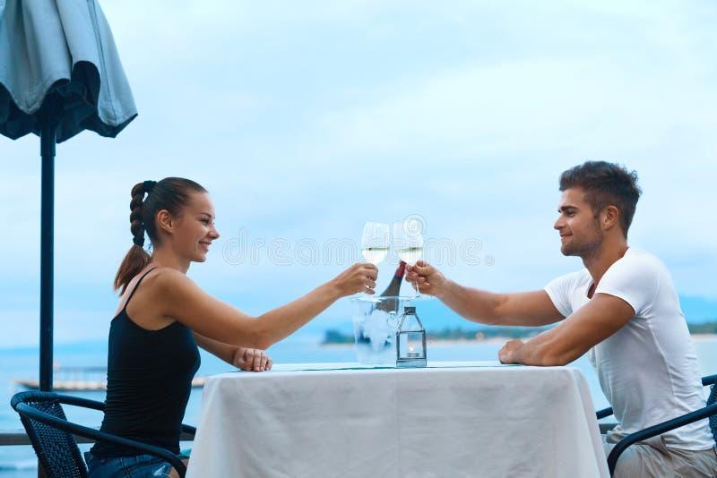 在爱的浪漫夫妇吃晚餐在海海滩餐馆 免版税库存照片