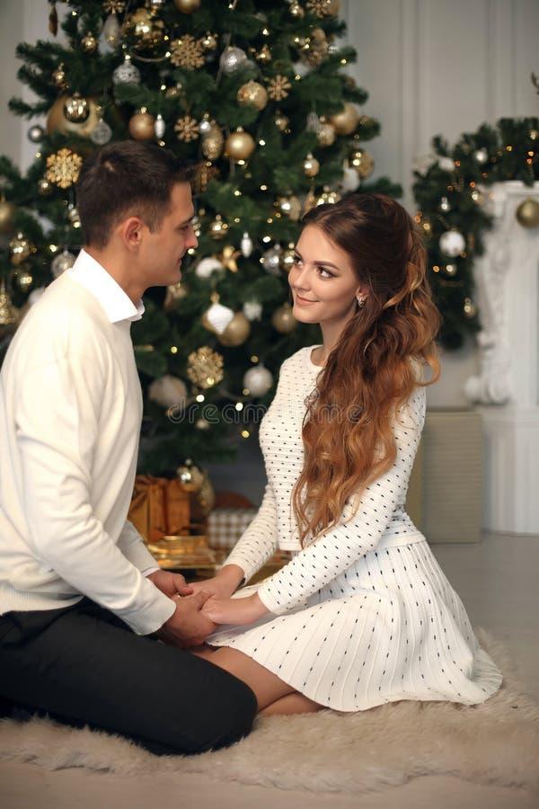 在爱的浪漫夫妇画象 拥抱由Xmas圣诞树的快乐的愉快的新婚佳偶 人提出婚姻他的女朋友 胜利 免版税图库摄影