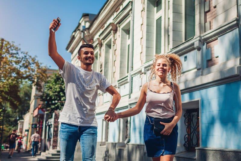 在爱的混合的族种夫妇走和谈话在城市街道上 获得愉快的夫妇垂悬和乐趣户外 库存照片