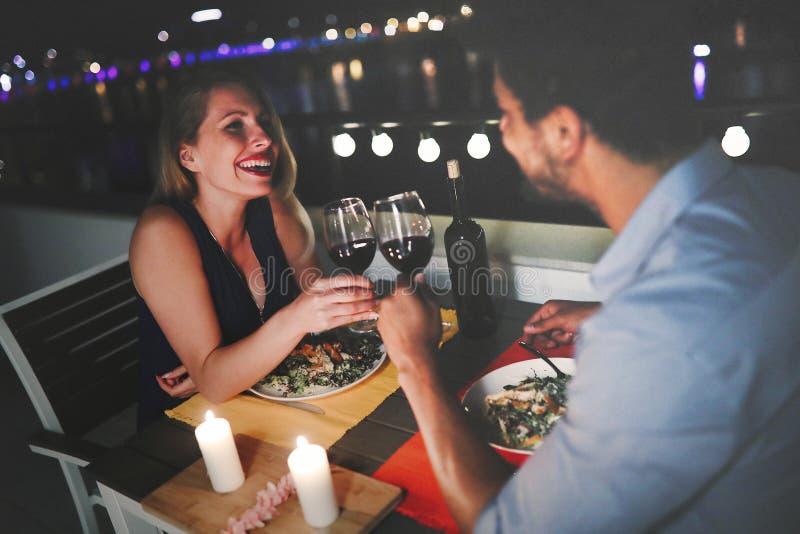 在爱的美好的夫妇吃浪漫晚餐在晚上 免版税库存照片