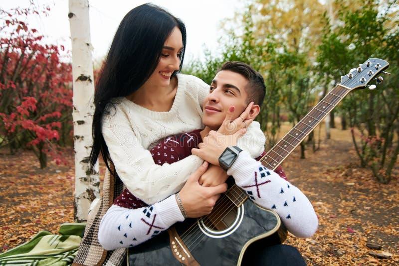 在爱的美好的夫妇在与吉他的自然 免版税库存图片