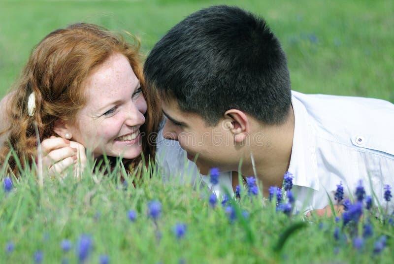 在爱的美好的年轻夫妇在一块绿色沼地 免版税库存图片