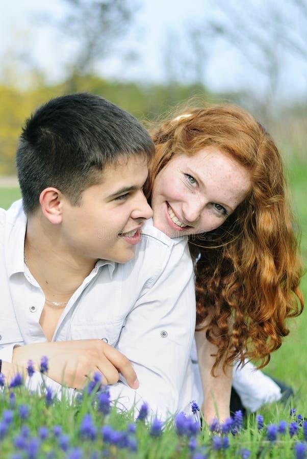 在爱的美好的年轻夫妇在一块绿色沼地 免版税图库摄影