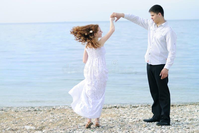 在爱的美好的年轻夫妇在海附近 免版税库存图片