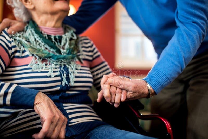 在爱的资深夫妇,老人照顾他的轮子的妻子 库存照片