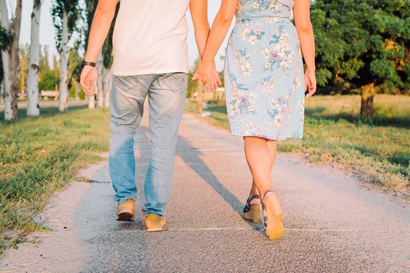 在爱的逗人喜爱的年轻夫妇握他们的手并且在公园走 免版税图库摄影