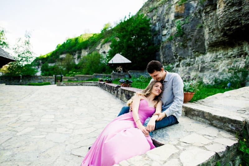 在爱的年轻夫妇一起坐一条长凳在夏天公园 愉快的未来,婚姻概念 葡萄酒 免版税库存照片