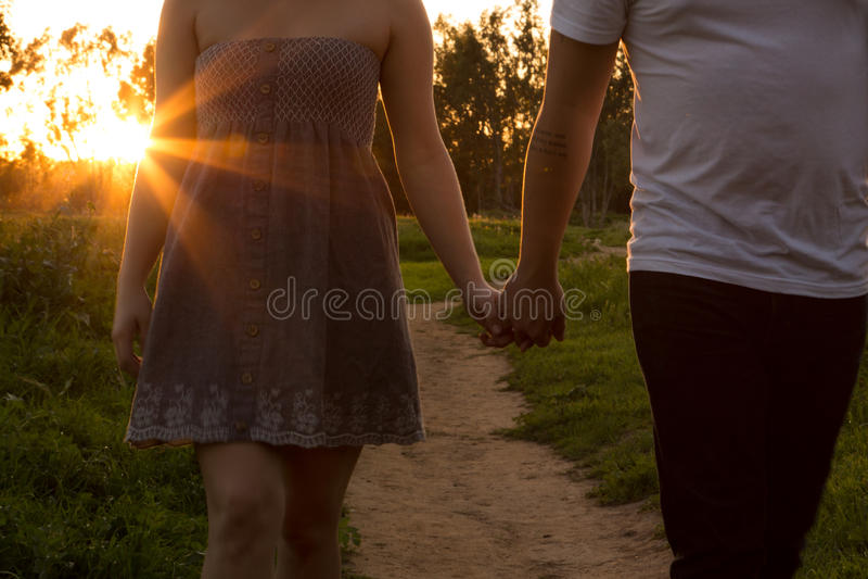 在爱的年轻夫妇在与太阳的一个领域通过树 库存照片