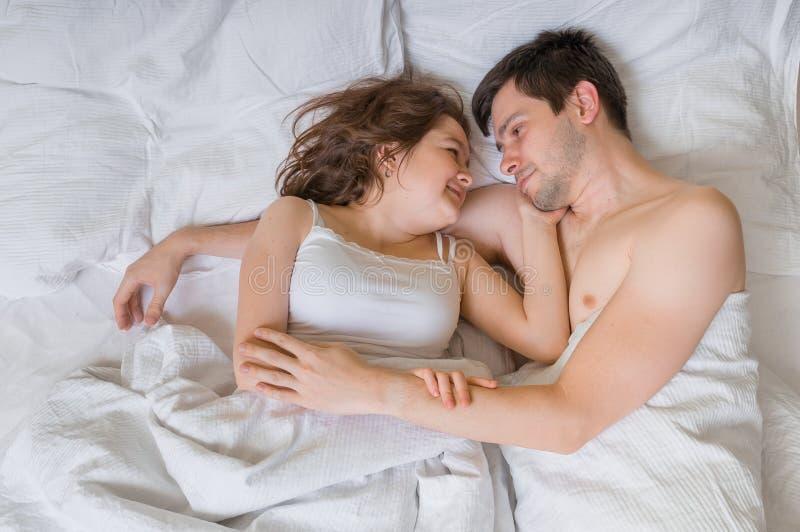 在爱的年轻夫妇在床和拥抱上在 他们在他们的眼睛看 免版税库存图片