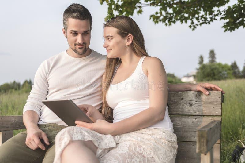 在爱的年轻夫妇室外在日落 免版税库存图片