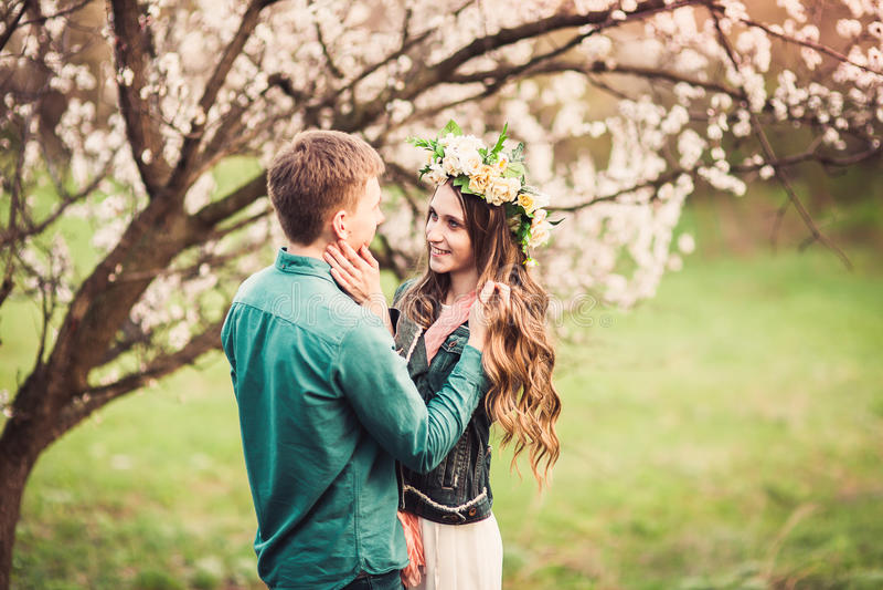 在爱的年轻夫妇有日期在桃红色开花树下 免版税库存照片