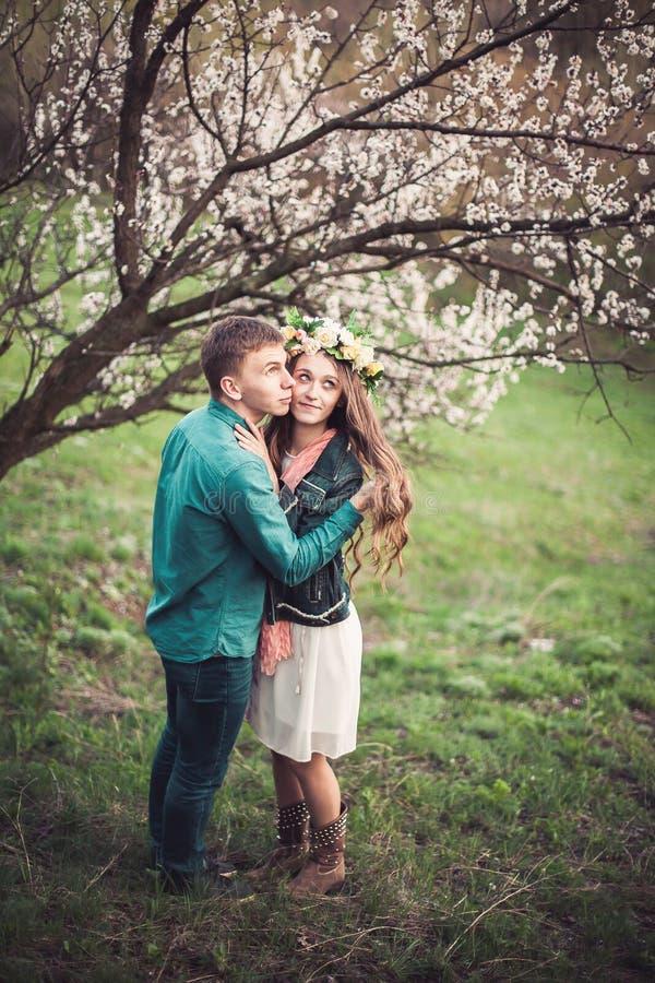 在爱的年轻夫妇有日期在桃红色开花树下 免版税库存图片