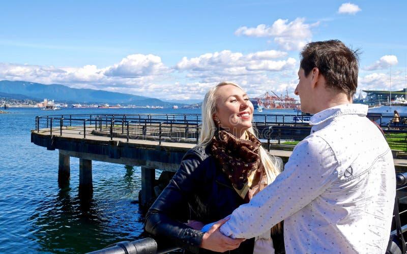 在爱的年轻夫妇由海 免版税库存图片