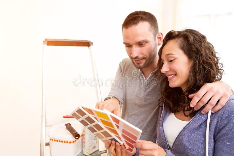 在爱的年轻夫妇移动了他们新的舱内甲板 免版税库存图片