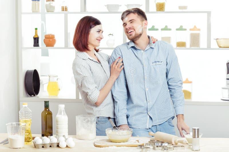 在爱的滑稽的夫妇烹调面团和获得乐趣用面粉在厨房里 免版税库存图片