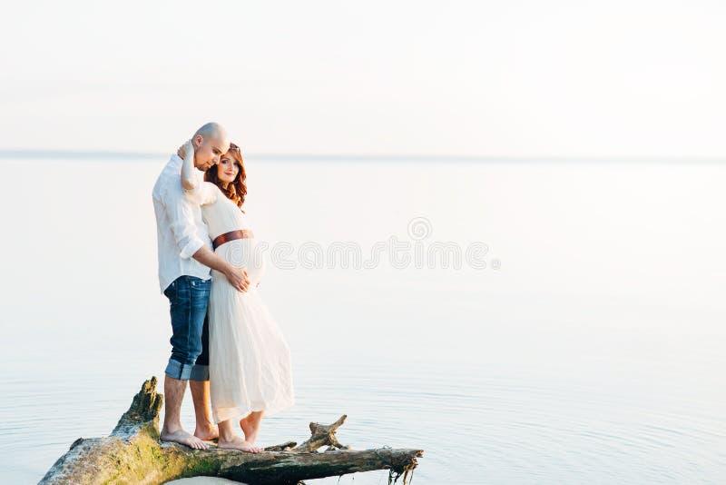 在爱的年轻美好的怀孕的夫妇在夏天晴朗的晚上 免版税库存照片