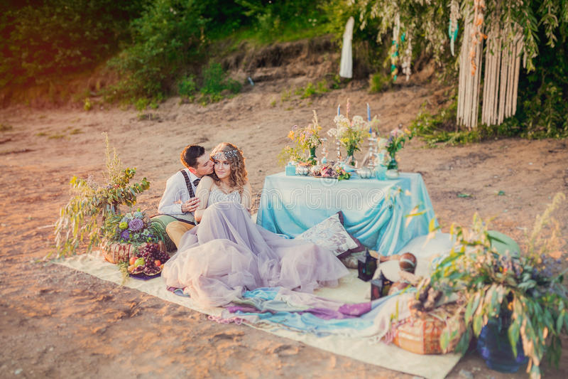 在爱的Boho别致的夫妇新娘和新郎 婚礼户外启发野餐,与饭桌和装饰在绿松石co 库存图片