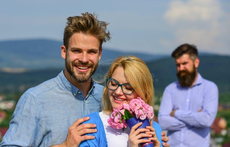 在爱约会的夫妇,当嫉妒的有胡子的欺诈他的人观看的妻子与恋人时 恋人拥抱室外调情的人浪漫史 库存照片