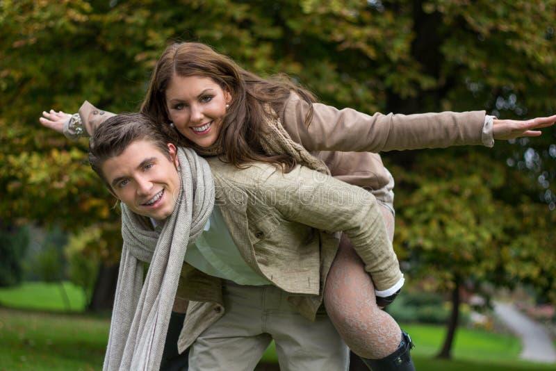 在爱肩扛的年轻夫妇在公园 库存照片