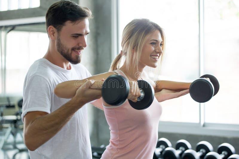 在爱行使的举重哑铃的年轻夫妇一起在健身健身房 体育人男朋友帮助女朋友锻炼 库存图片