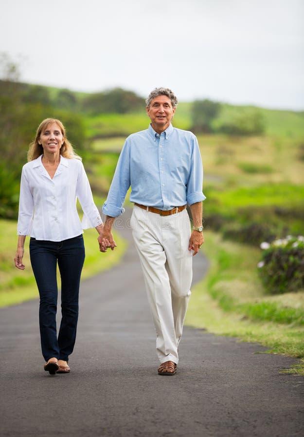 在爱走的成熟中年夫妇 免版税库存照片
