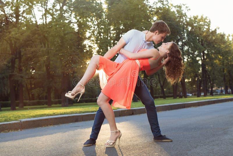 在爱跳舞的愉快的年轻夫妇在日落点燃 库存图片