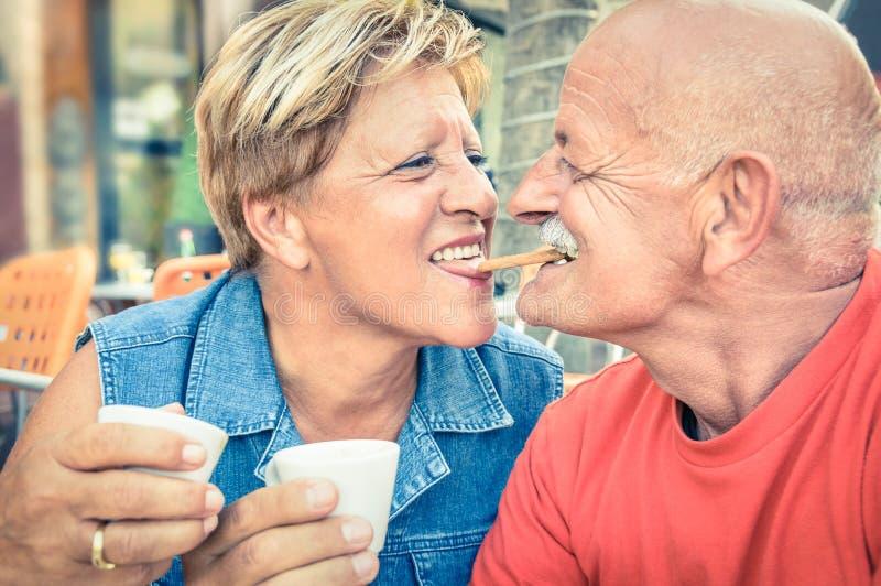 在爱饮用的coffe的愉快的嬉戏的资深夫妇在酒吧 免版税库存图片