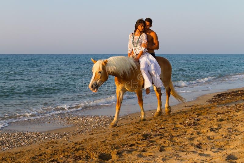 在爱骑乘马的有吸引力的夫妇在海滩。 免版税库存图片
