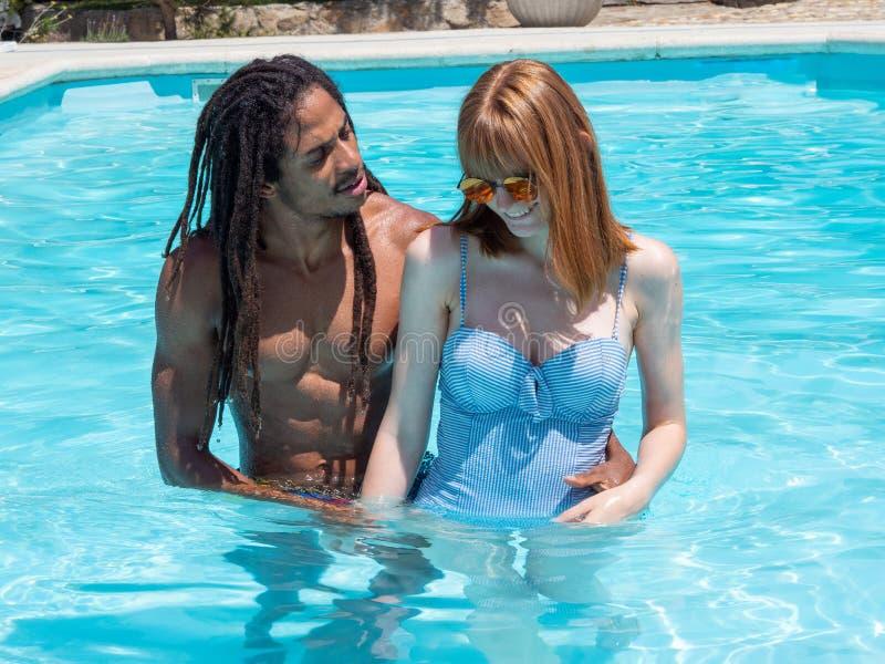 在爱,在水池的戏剧的人种间夫妇 非常白色的女孩和红色头发和男孩黑色 库存图片