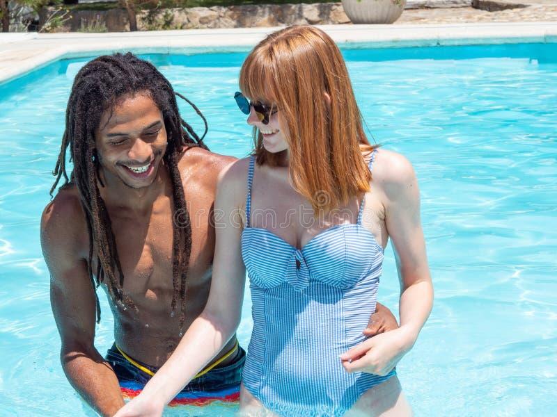 在爱,在水池的戏剧的人种间夫妇 非常白色的女孩和红色头发和男孩黑色 免版税库存照片