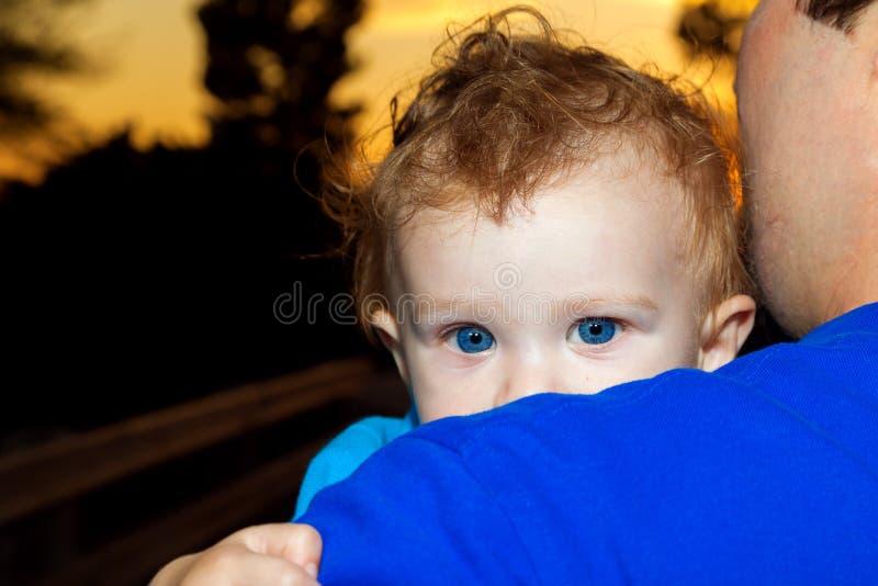 在爸爸肩膀的婴孩偷看  免版税库存照片