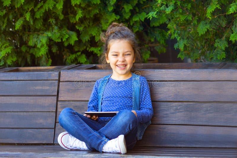 在片剂户外和微笑的女孩戏剧 运作的Outsid 免版税库存图片