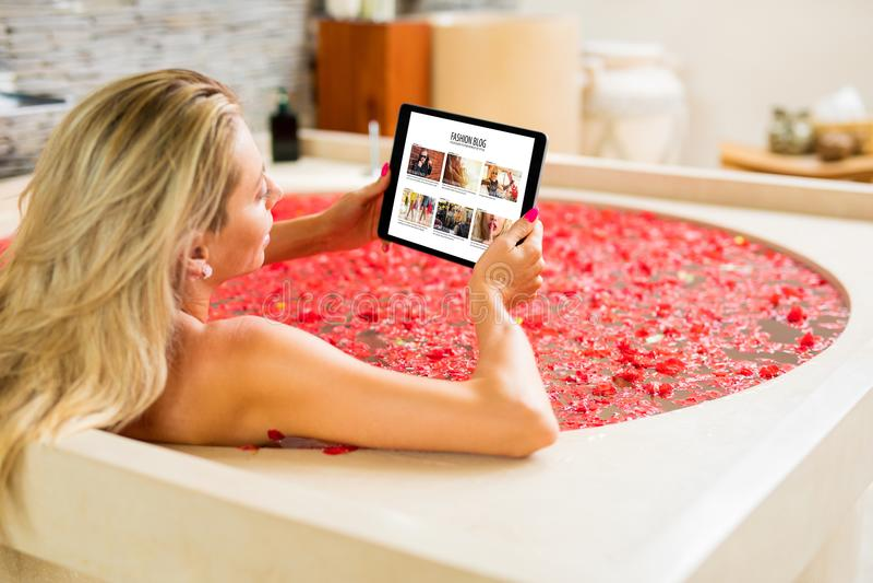 在片剂的妇女读书,当洗浴时 免版税图库摄影